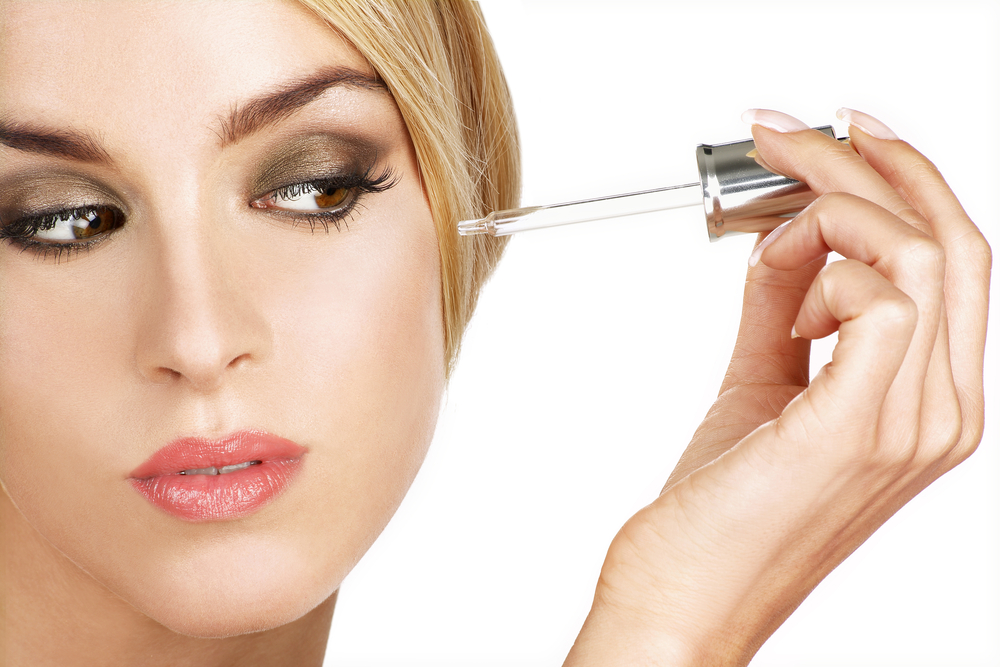 Woman applying a serum on her skin.