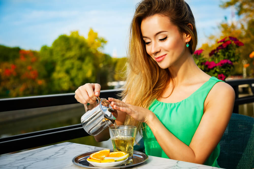 Smiling woman pouring tea into cup