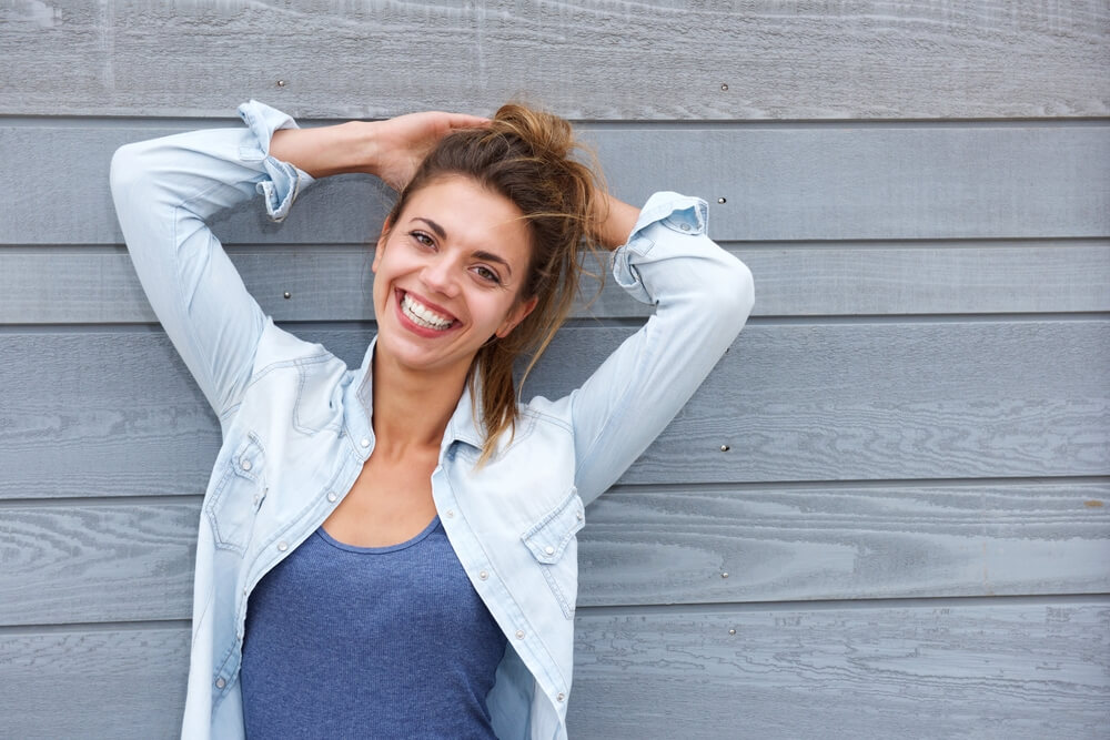 Smiling confident woman with arms on her head