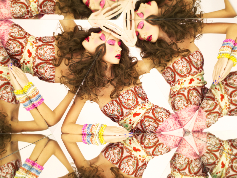 Bright young brunette in kaleidoscope of reflections