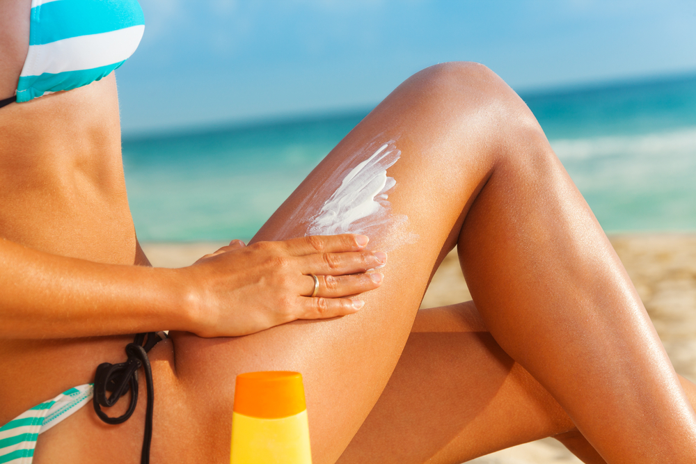 Putting sunscreen on her legs out by the beach