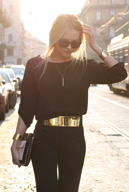 Wide gold belt completes a black outfit