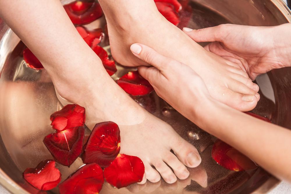 Woman soaking her feet in water.