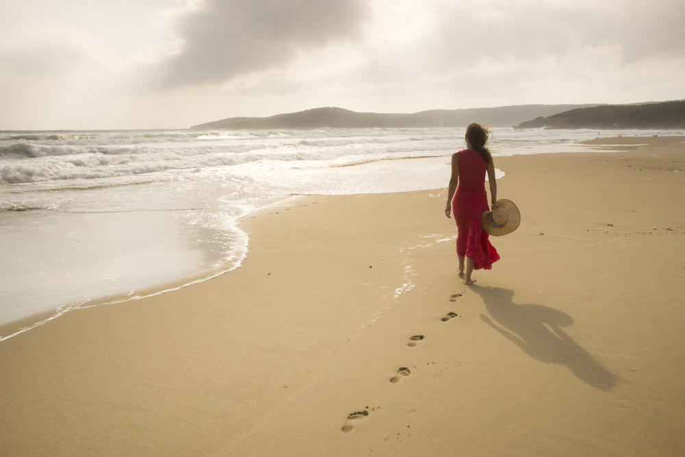 Woman walking barefoot on the sand