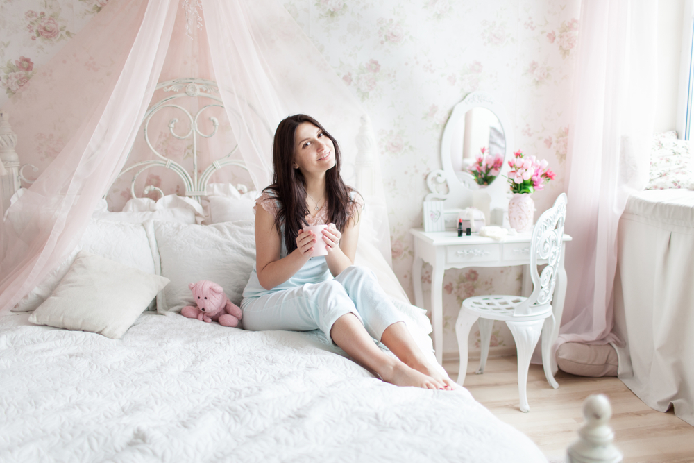 Woman sitting on a bed with lots of pillows