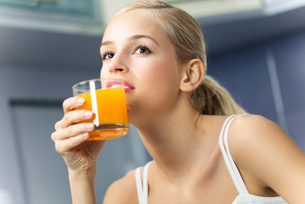 Woman drinking orange juice.