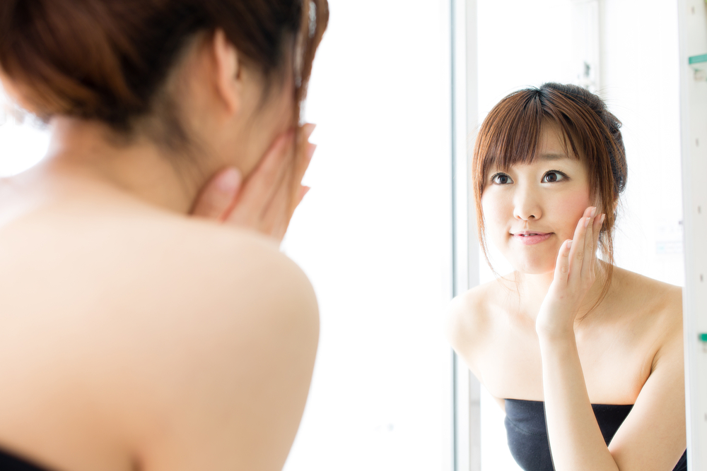 Asian woman looking into the mirror and touching her cheek. Makeup theme.