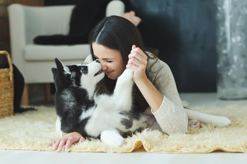 Woman loving her dog at home