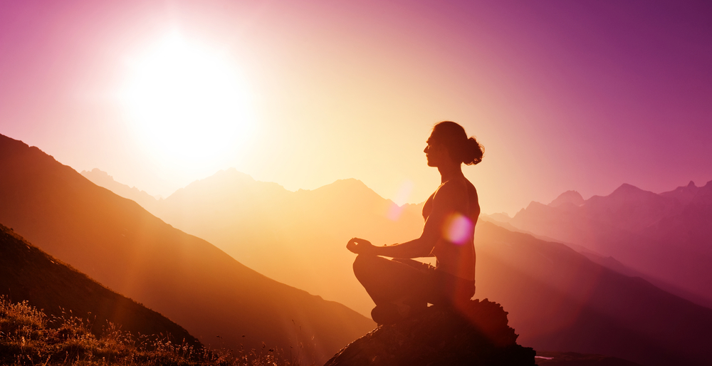 Meditating on a hill with the sunshine for better skin