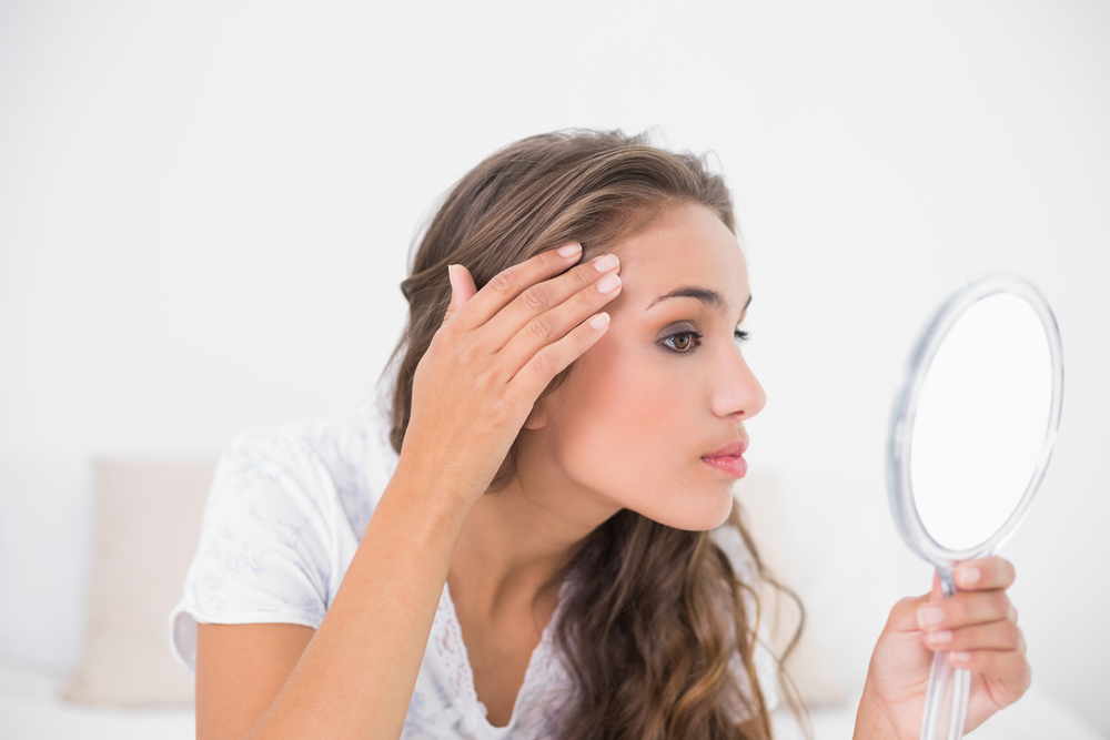 Woman looking at herself in the mirror before going to bed.