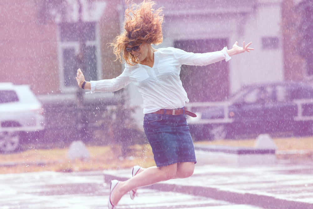 Woman jumping in puddle