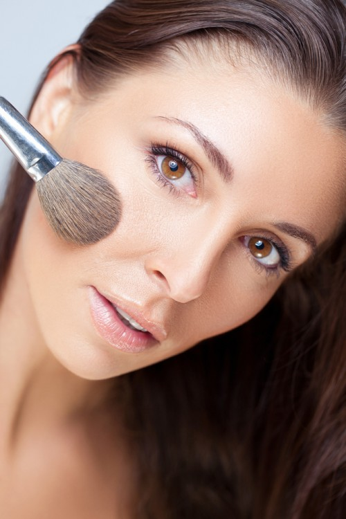 Woman using a makeup brush to apply foundation