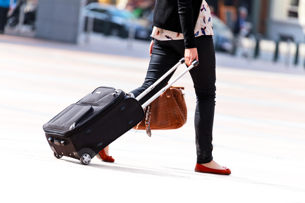 Woman wearing flats carrying her luggage.