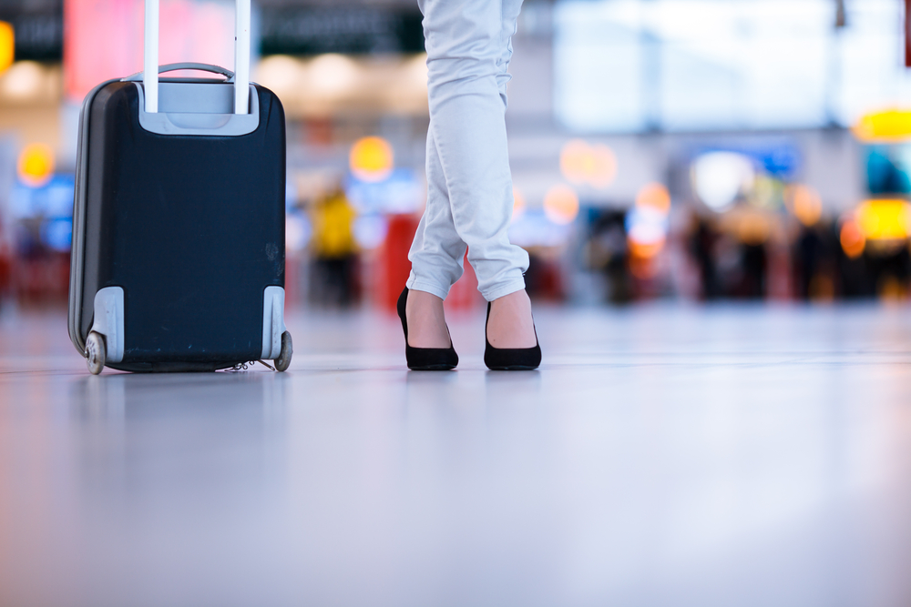 Woman walking with her luggage in an airport.