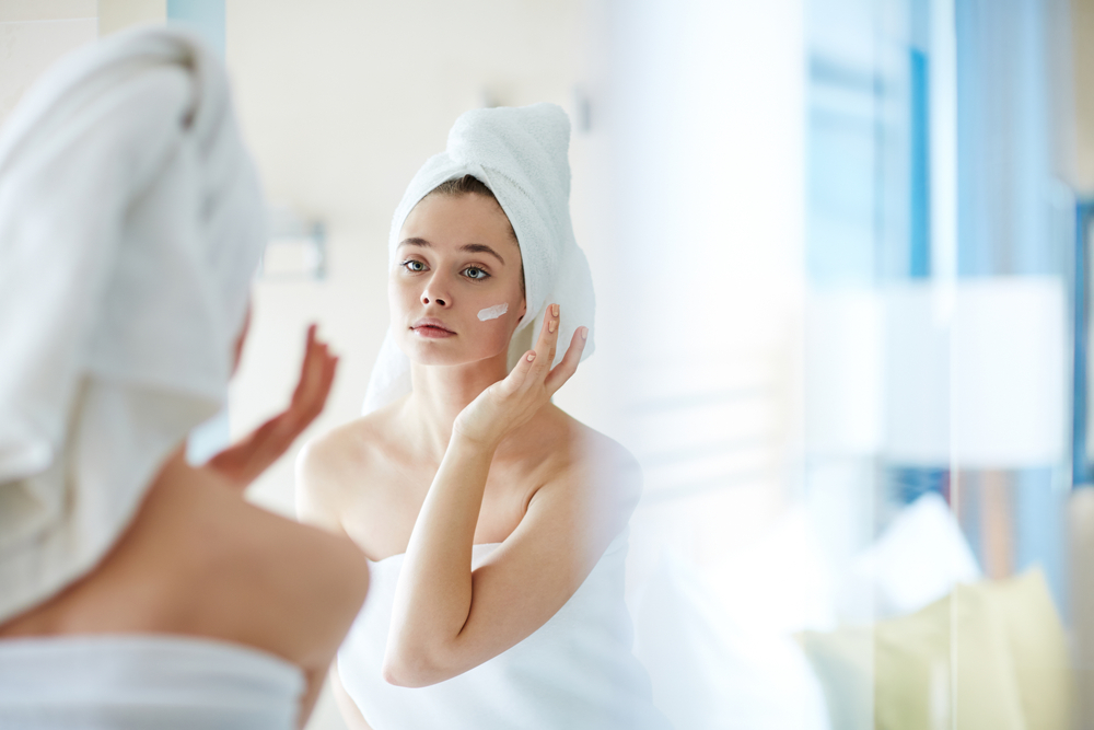 Woman putting lotion on face