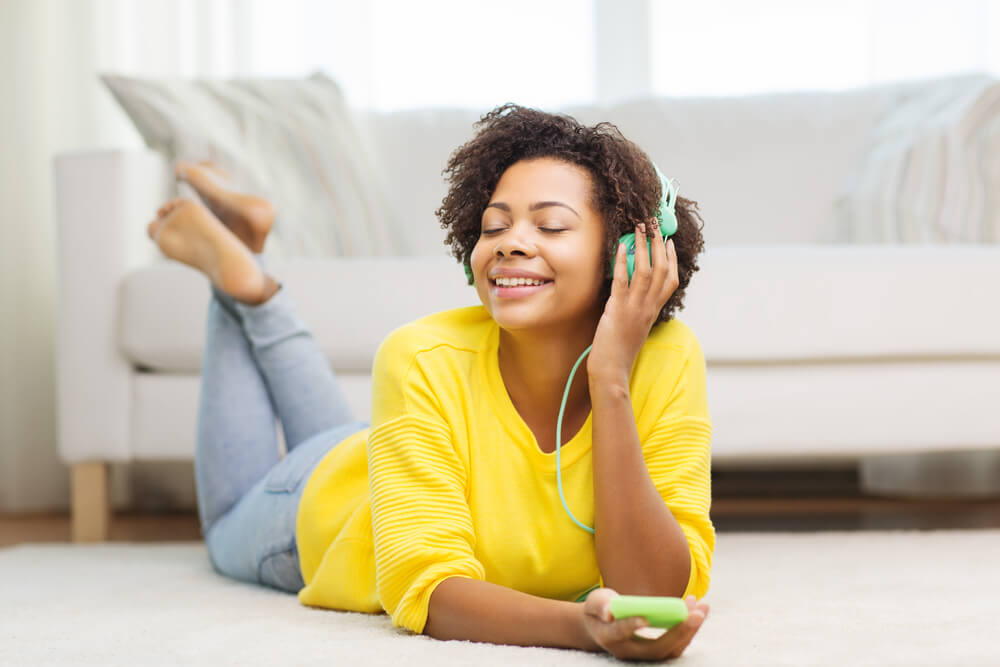 Happy woman listening to music with headphones at home