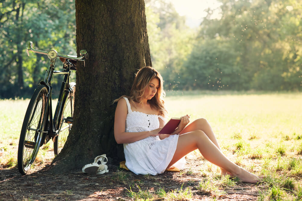 Woman reading while leaning against a tree