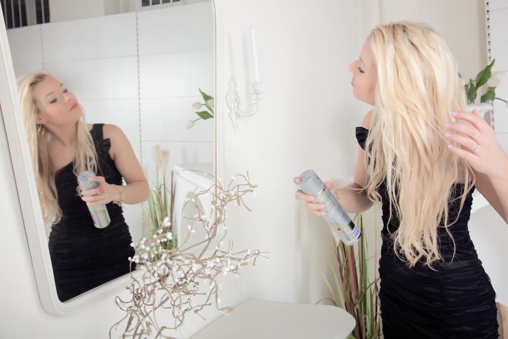 Woman using a hair spray.
