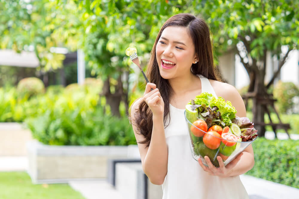 Smiling woman with a bowl of salad outdoors