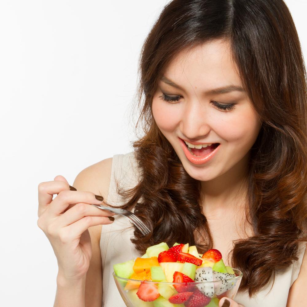 Asian woman eating fruit salad.