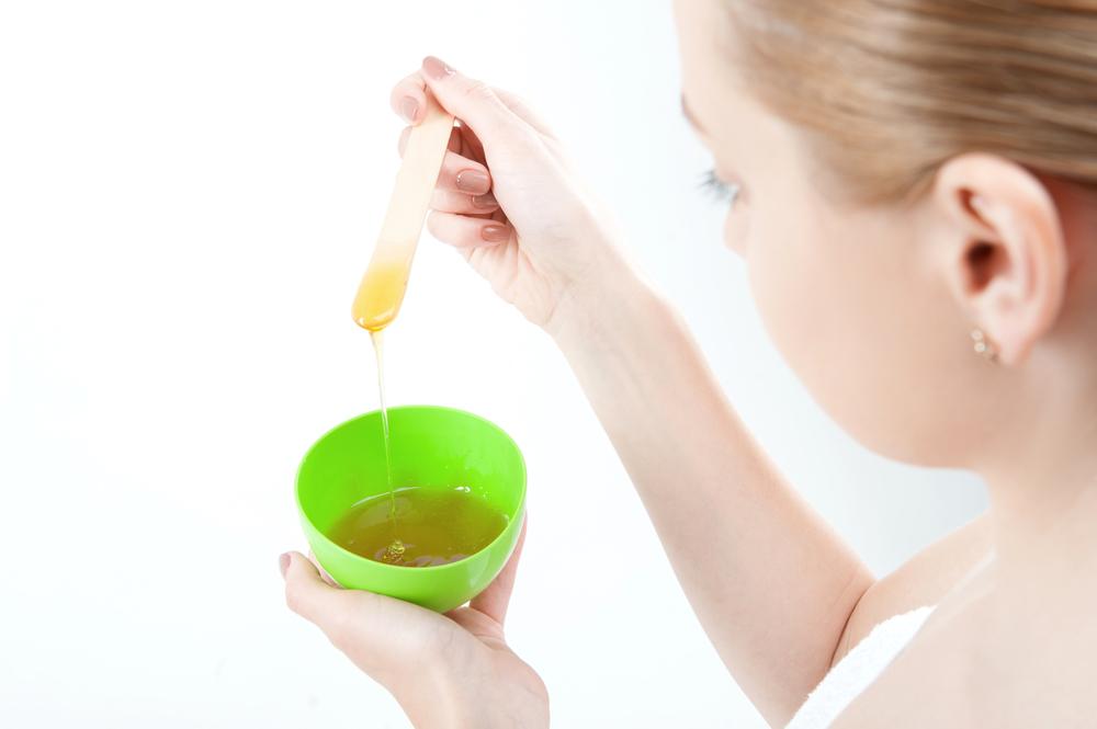 Woman preparing a honey mask.
