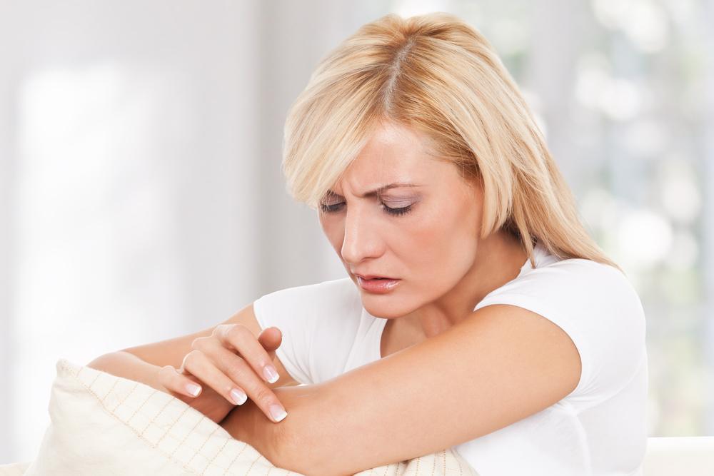 Woman examining her dry skin.