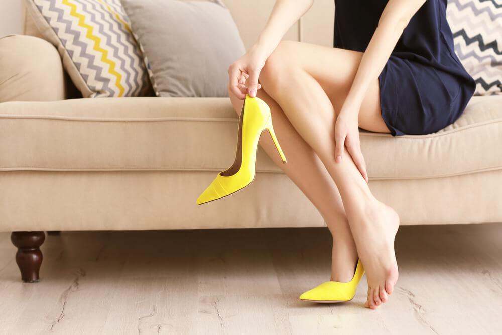 Woman taking off yellow heels