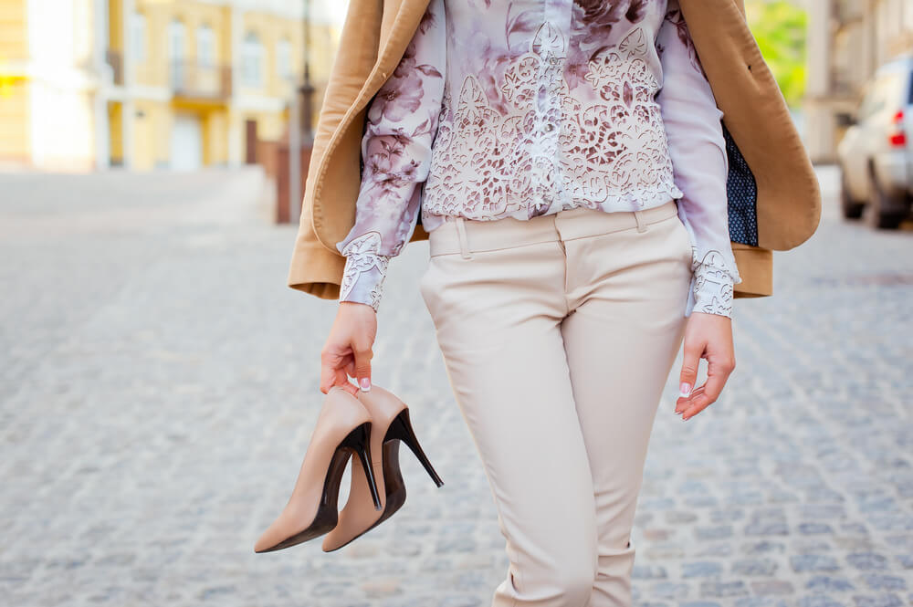 Woman walking while holding a pair of heels