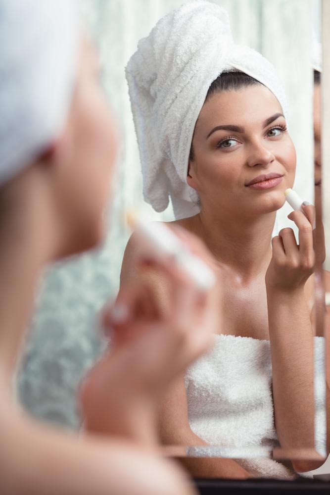Woman using lip balm.