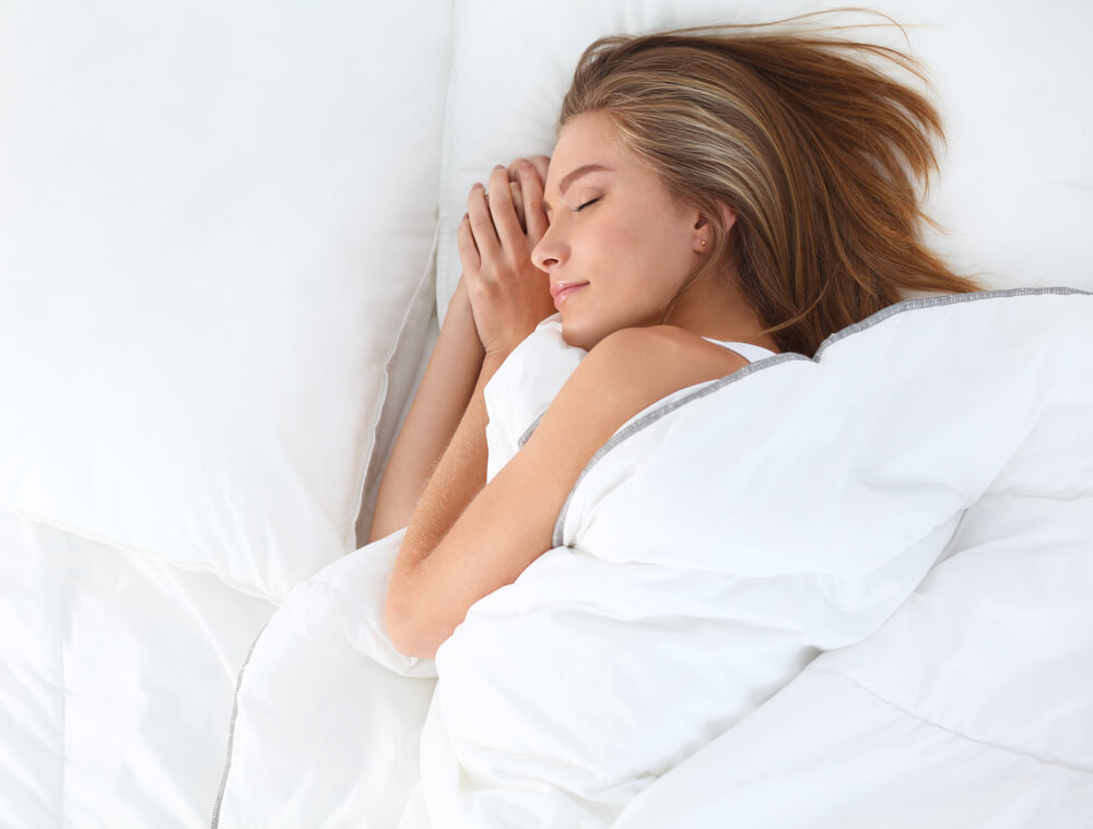 Woman sleeping on white bedsheets and blanket