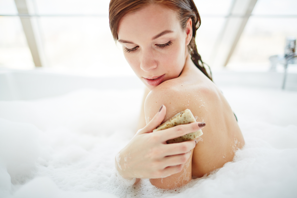 Woman exfoliating in bath