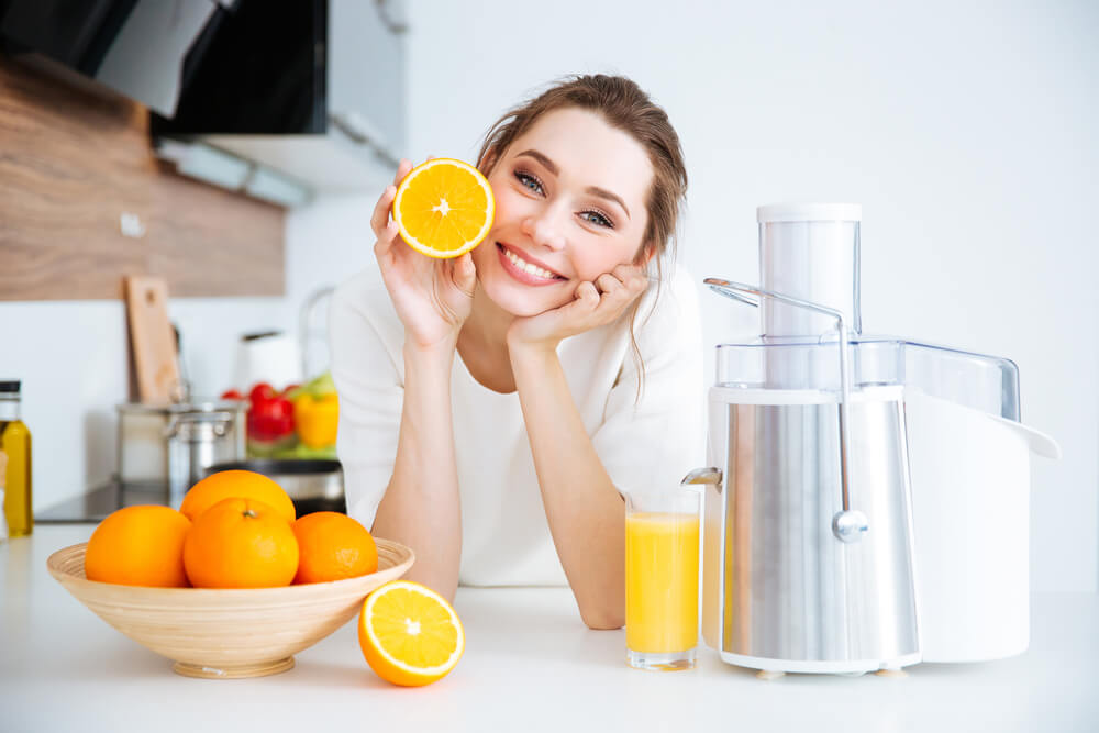 Smiling woman posing with an orange in kitchen