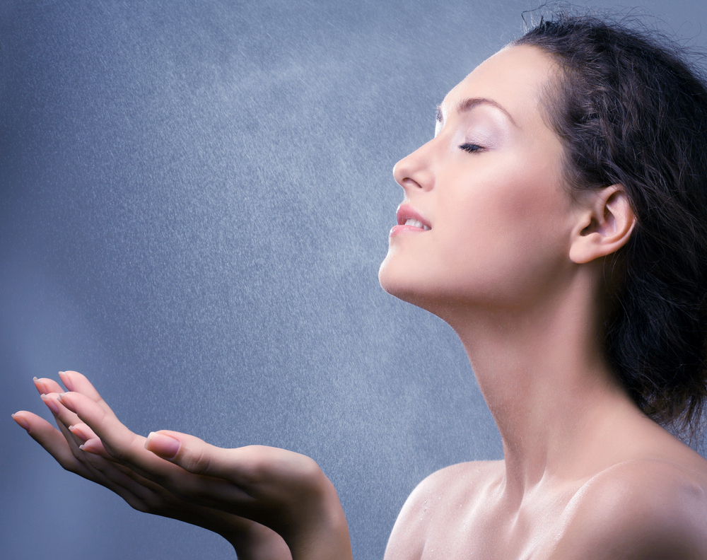 Woman spraying her face with water