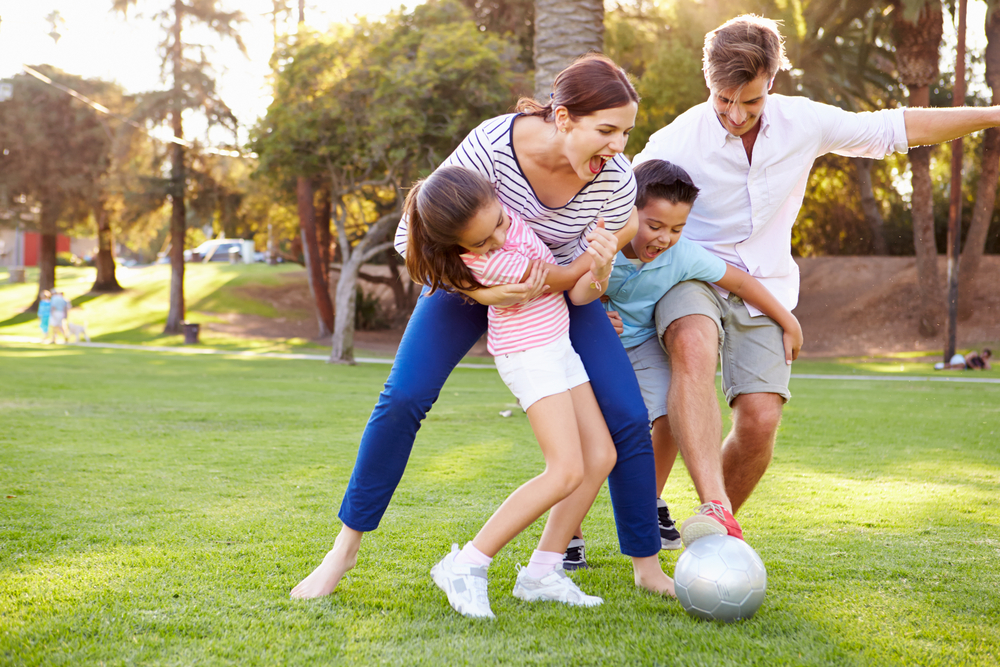 Family playing soccer in the park