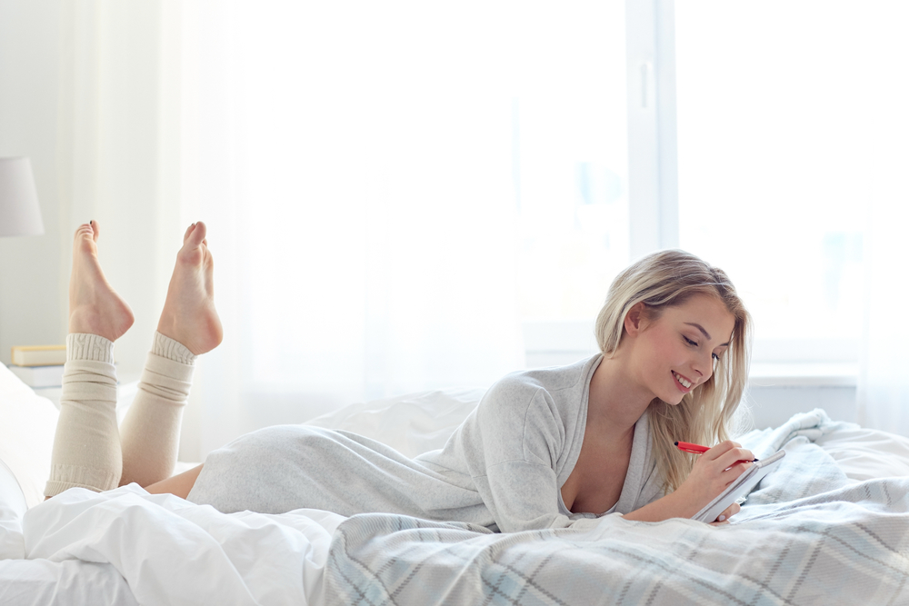 Woman writing list on bed