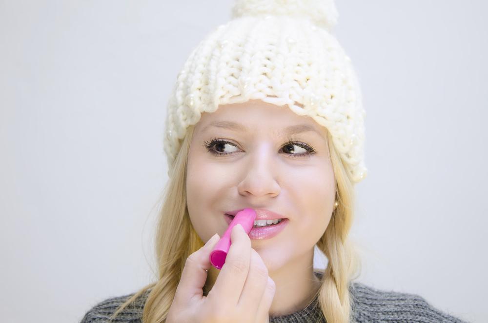 Woman applying lip balm.