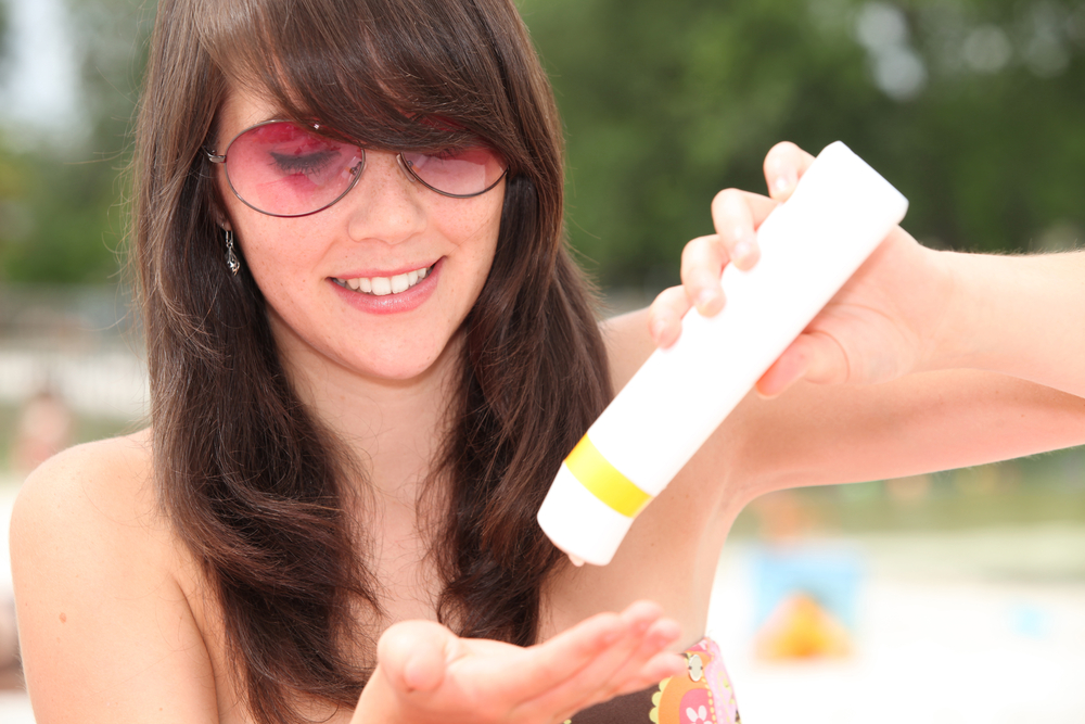 Woman wearing sunglasses applying sunscreen on her body.