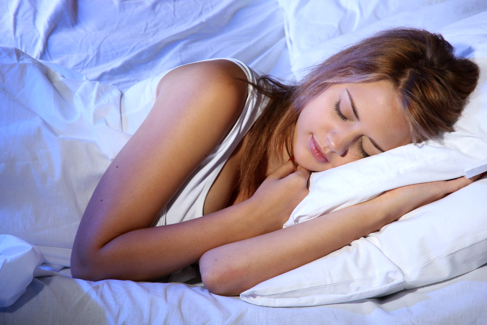 Woman wearing white clothes sleeping in her bed.