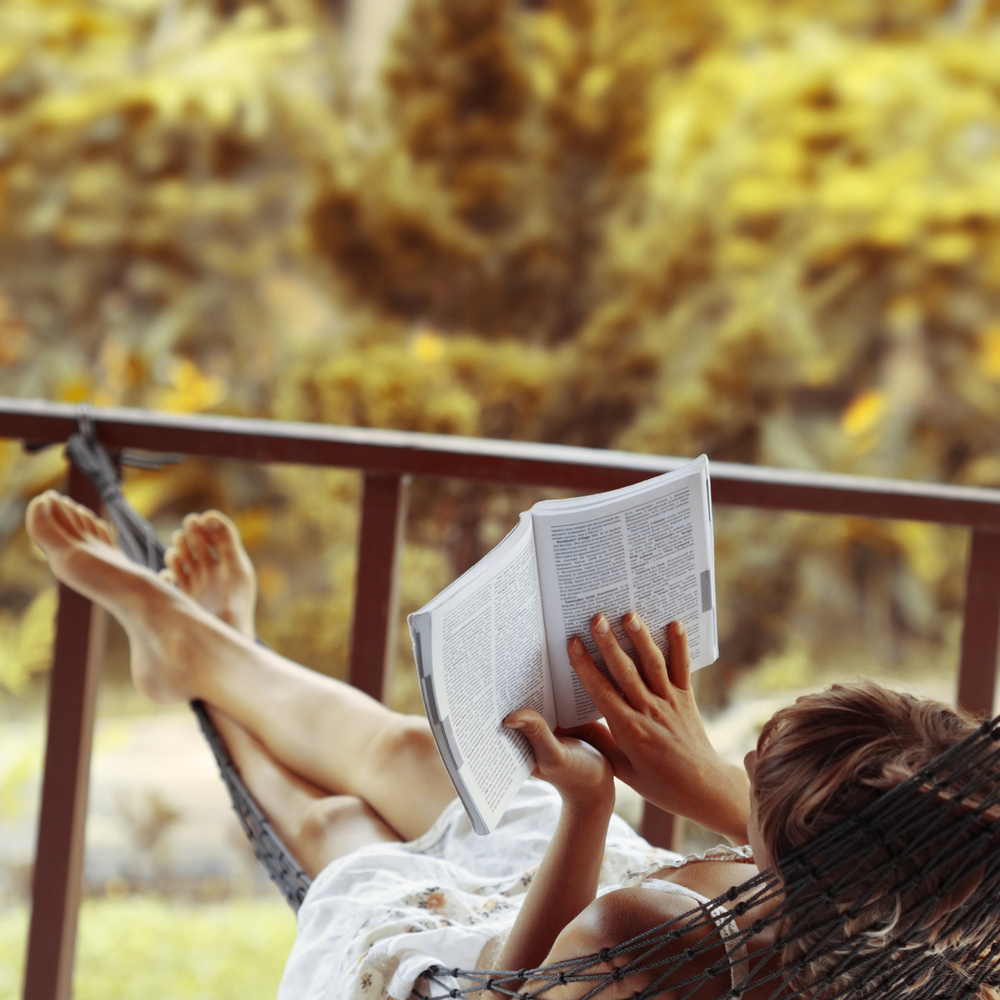 Woman reading a book while lying in a hammock in her garden.