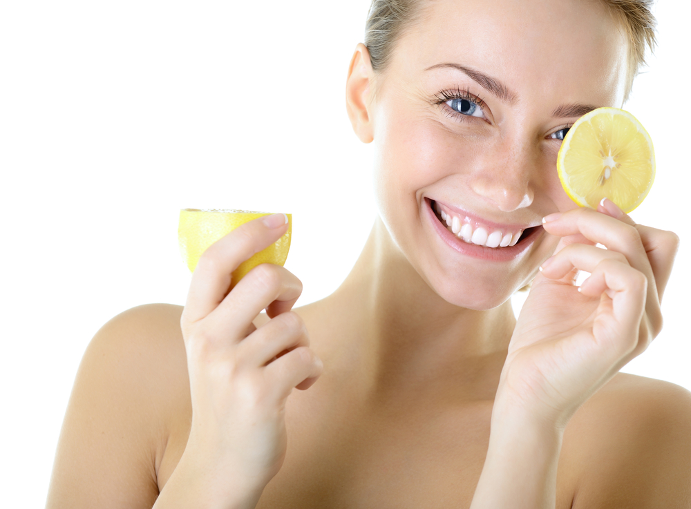 Smiling woman holding a slice of lemon on her eyes.