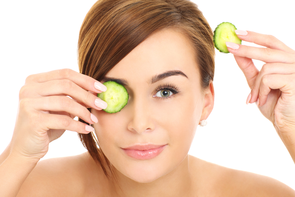 Beautiful woman applying cucumber on her eyes as a part of her eye care routine.