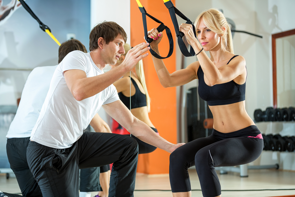 Woman enjoying a resistance training session at the gym with a personal instructor.
