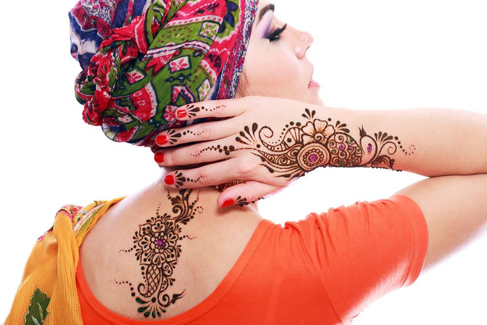 Beautiful woman wearing a Middle East styled turban showing off her henna designs.