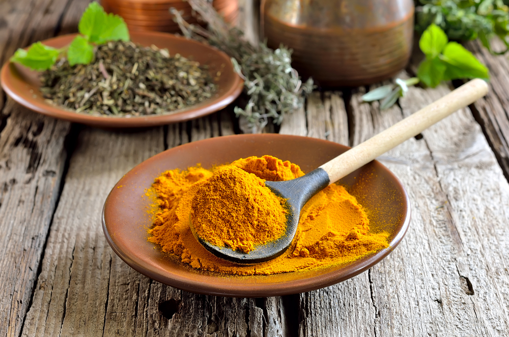 Image of turmeric powder in a wooden spoon.