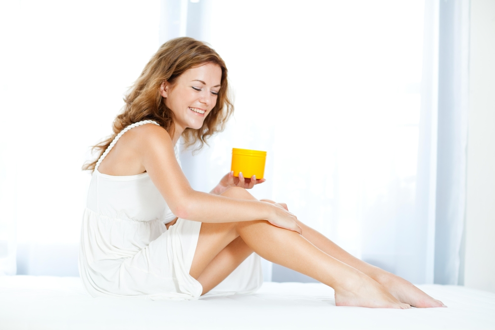 Beautiful woman applying moisturizer on her legs.