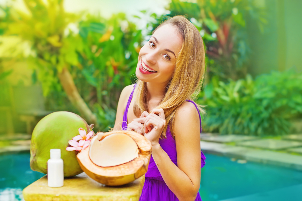 Happy woman standing behind a coconut in a beautiful natural  background.
