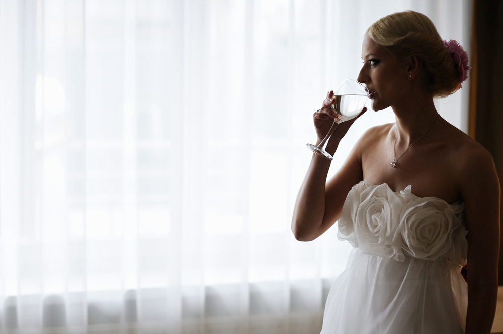 Bride drinking water from a glass.